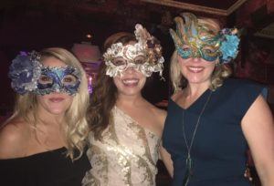 Three women in fancy costume masks and cocktail dresses smile at the camera.