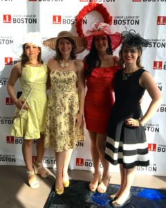 Four women in short fancy dresses and large brimmed decorated hats standing in front of a background with the Junior League of Boston logo and a red flower garland