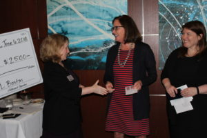 JL Boston president Karen Page shakes the hand of a smiling grant recipient while JL Boston Melissa Herman looks on