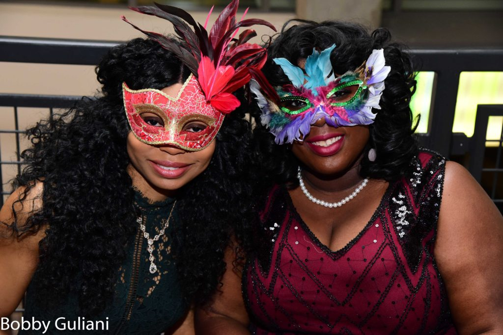 Two smiling women wear feathered masquerade masks