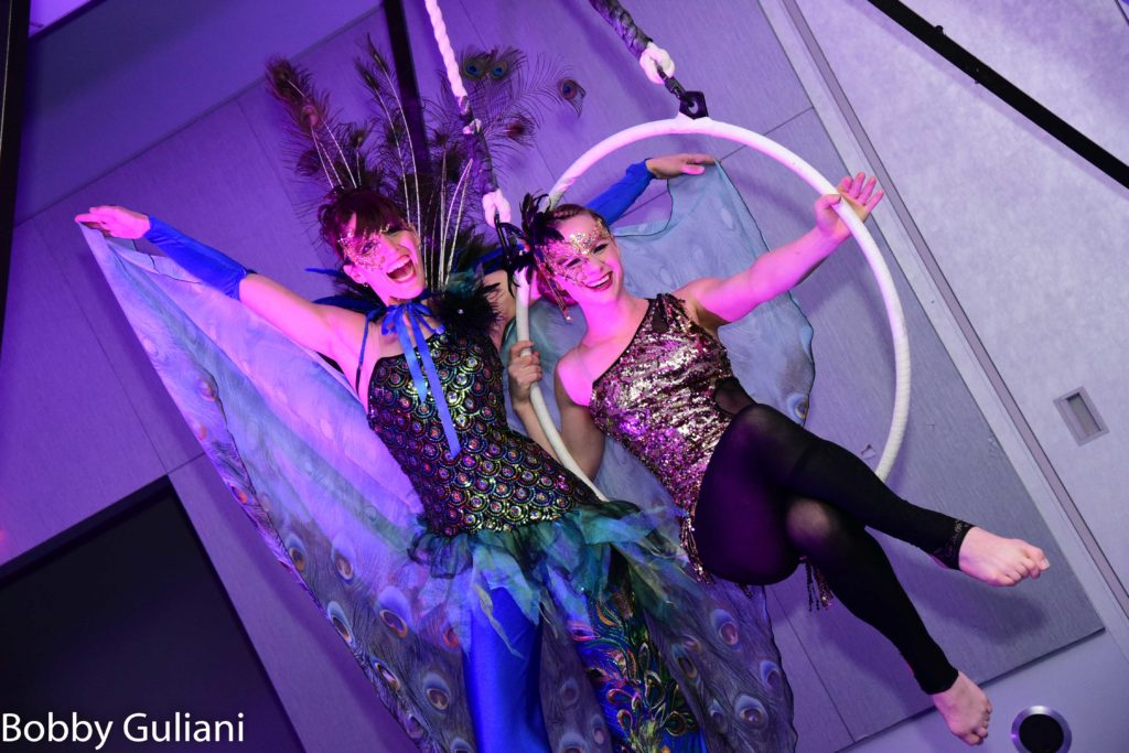 A woman on stilts and a woman on an aerial hoop smile at the camera while wearing masquerade masks and sequined outfits