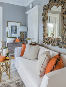 A beautifully decorated living room with a light colored couch, bright orange accent pillows, and an ornate decorative mirror