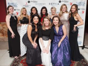 A group of women in formal gowns pose smiling in front of a banner with event sponsor logos at a past Junior League of Boston Charity Gala