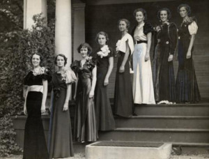 Black and white image of eight women in long dresses standing on the steps of a building
