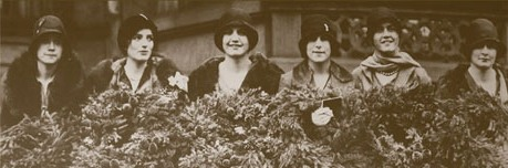 Black and white image of six women in 1920s style hats carrying evergreen wreaths