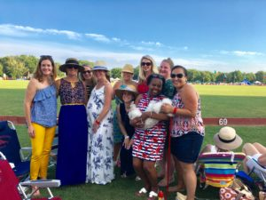 A group of ten JL Boston members at Newport Polo Grounds for Picnic and Ponies event, standing in front of a green field and blue sky