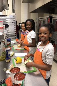 Three adolescent girls stand along a counter wearing orange aprons and chopping vegetables. They are participants in one of the Junior League of Boston community programs supported by your donation