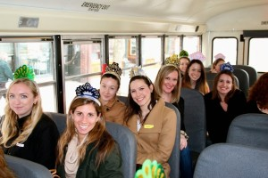 Smiling women wearing party hats are seated on a bus. The image shows Junior League members touring community programs throughout the city of Boston