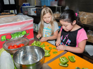 Two young girls work cutting green bell peppers on placemats as part of a Junior League of Boston community program that your donation could support