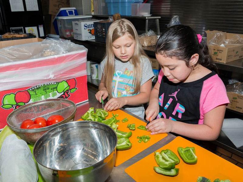 Two young girls cut green bell peppers on cutting boards as part of a Kids in the Kitchen session