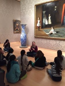 A woman sits cross-legged on the ground in an art museum in front of a large painting, gesturing with her hands. A group of adolescent girls sit on the floor around her and watch