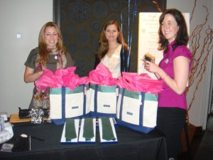 Three smiling JL Boston volunteers with gift bags at an event