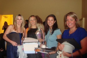 Four women volunteers holding raffle items at an event and smiling