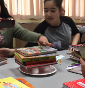A STEM program participant tests how many books can be stacked on eggshells before they crack.